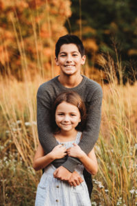 grand rapids michigan family photography session outdoors with a brother and sister hugging