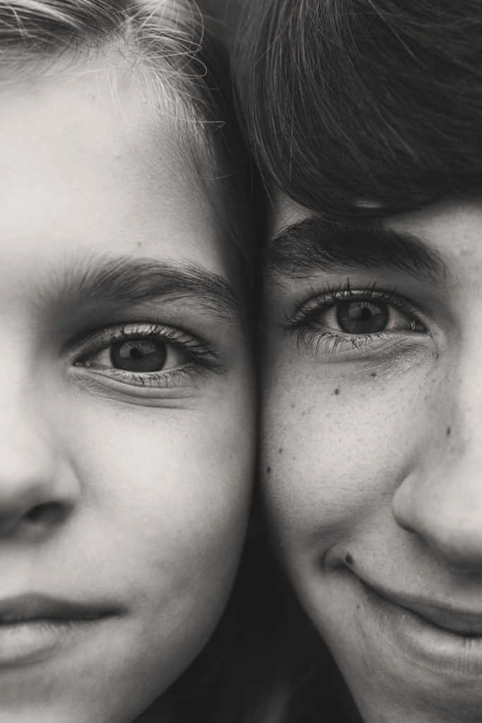 family photography, black and white of siblings sitting cheek to cheek