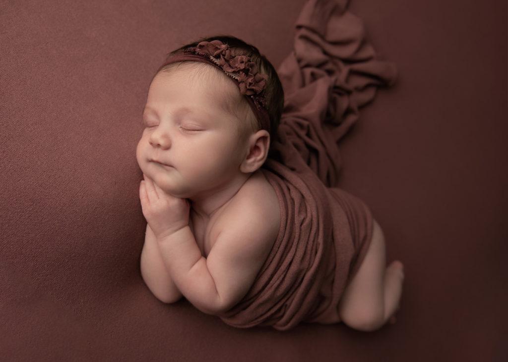 Newborn Photography, sleeping baby on burgundy background